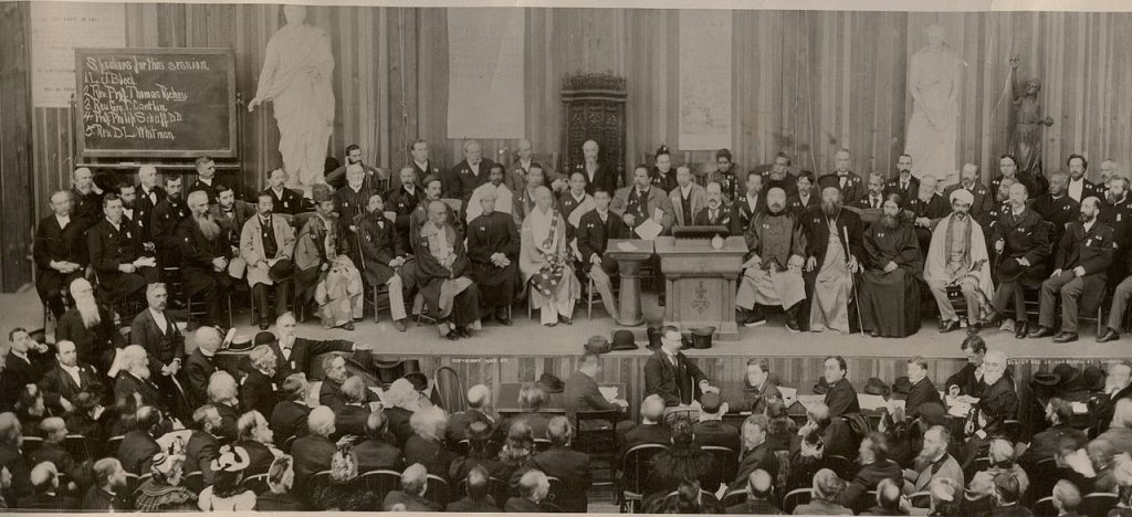 A large group of men sitting on a stage. The audience is also largely male, with a few women many rows back.