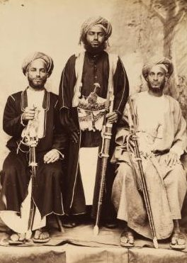 Three men, two seated on standing. They are all holding weapons.