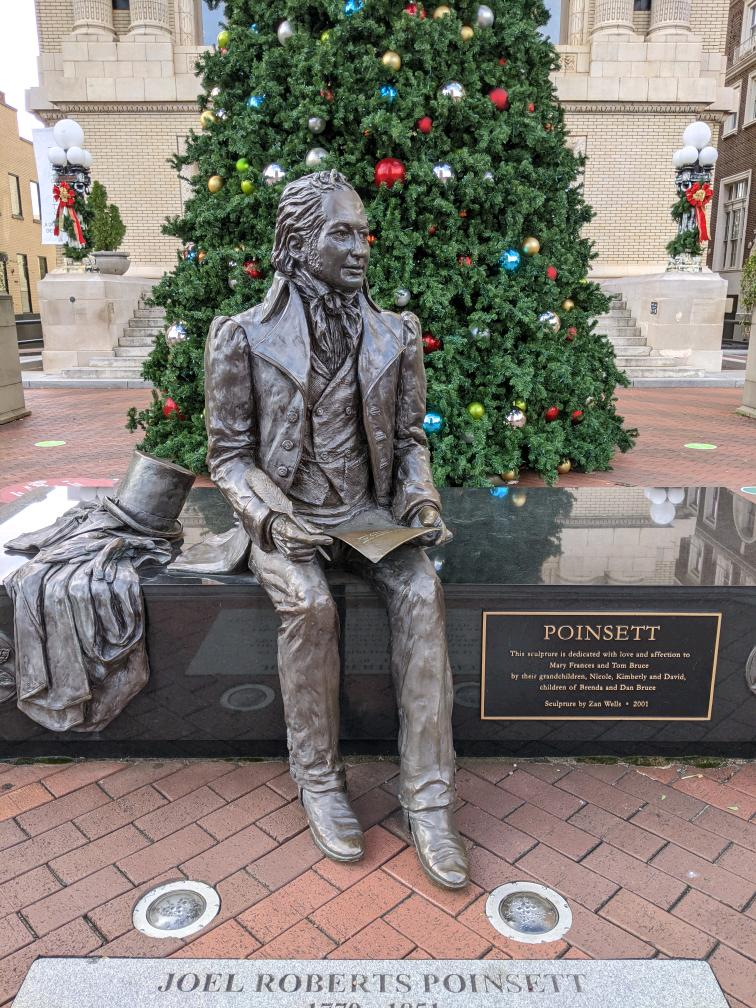 Photograph of Joel Poinsett statue in downtown Greenville, SC, with Christmas tree behind the statue.