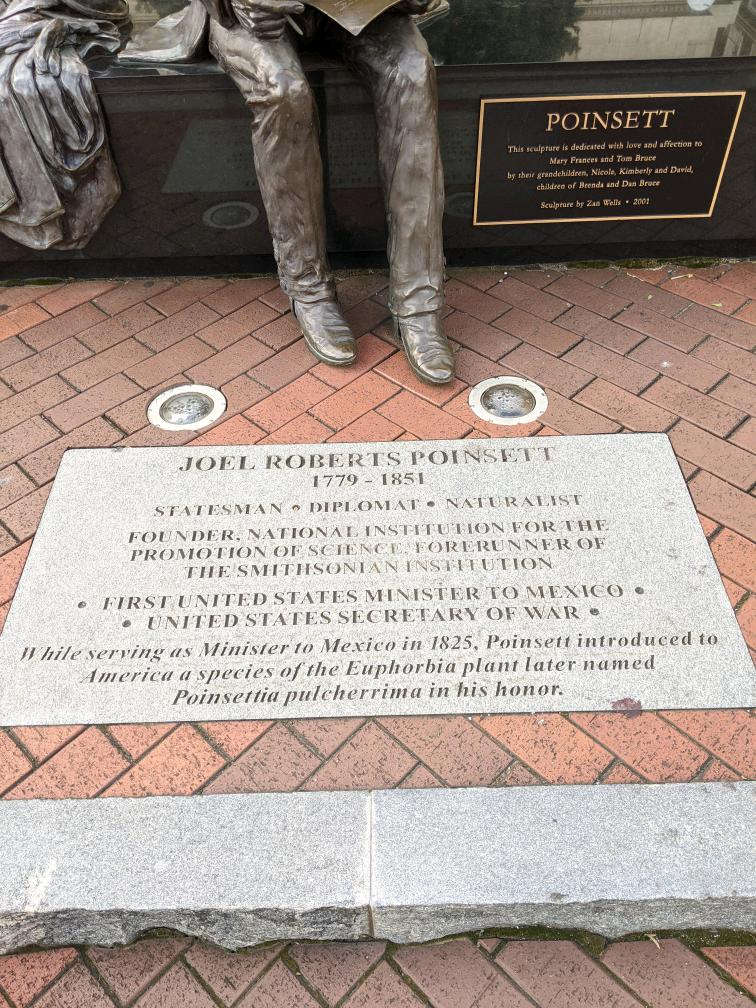 "Plaque at foot of Joel Poinsett statue, downtown Greenville, SC. It reads, ""Joel Roberts Poinsett, statesman, diplomat, naturalist, founder, National Institution for the Promotion of Science, forerunner of the Smithsonian Institution."""